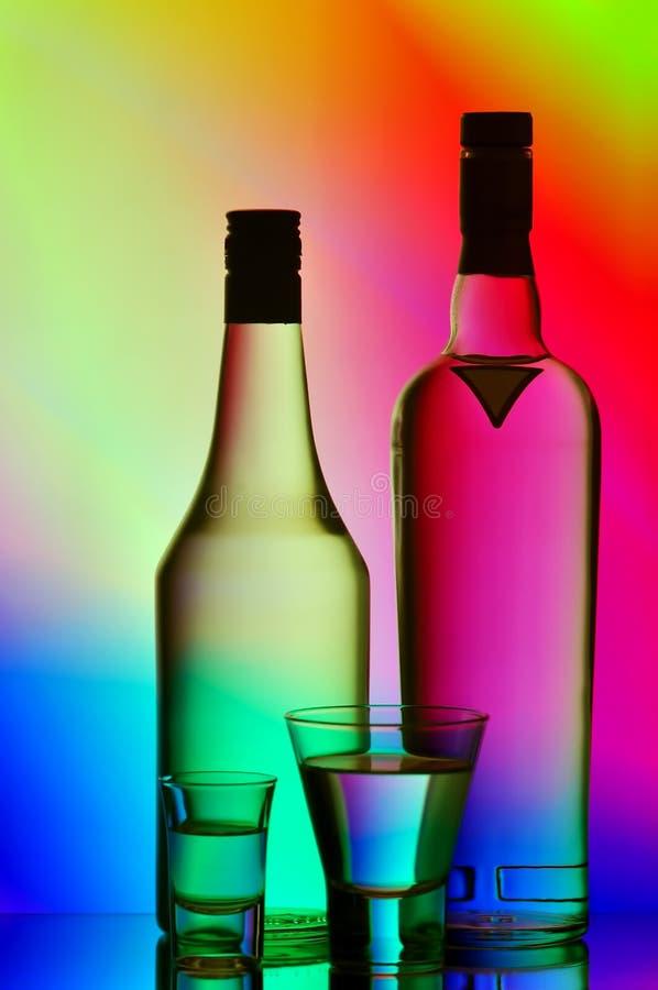 Liquor bottles and shot glasses royalty free stock photos