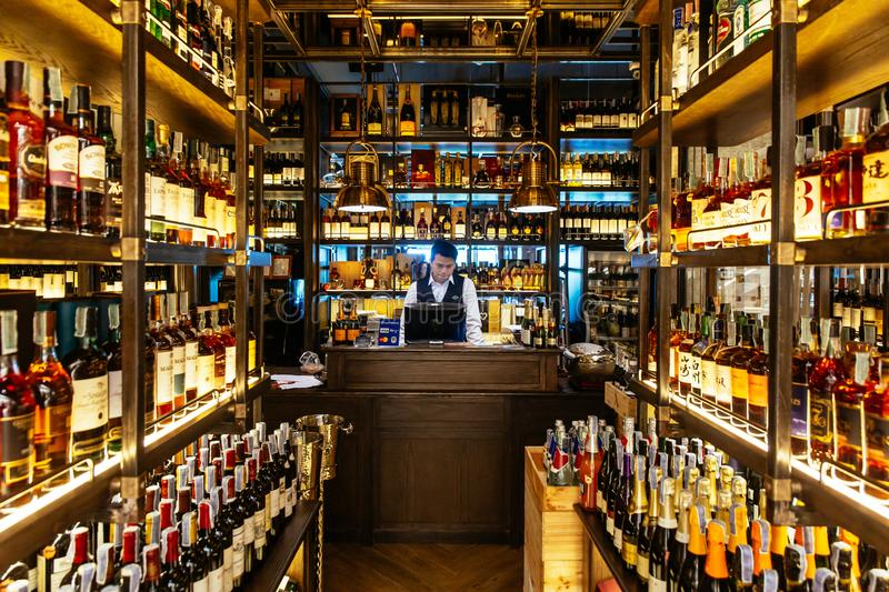 Liquor cellar inside the restaurant with sommerlier at cashier counter for help and giving information.  royalty free stock image