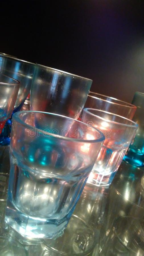 Liquor glasses of various colors blue and pink illuminated and suitable for drinking alcoholic beverages at home or in a bar or re stock photo