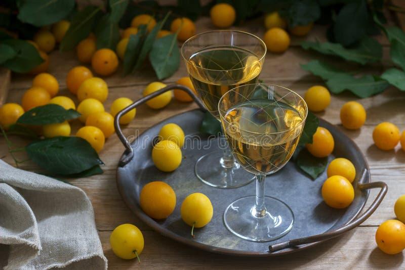 Liquore della ciliegia susina in piccoli vetri e ciliegia susina su un fondo di legno Stile rustico fotografia stock