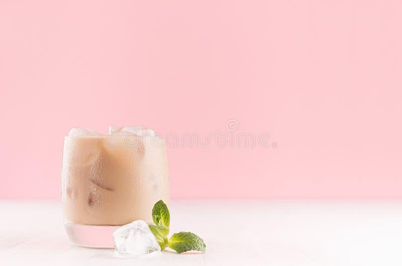 Liquore di Baileys in vetro appannato con i cubetti di ghiaccio e la menta verde su fondo rosa pastello e tavola di legno bianca, fotografia stock