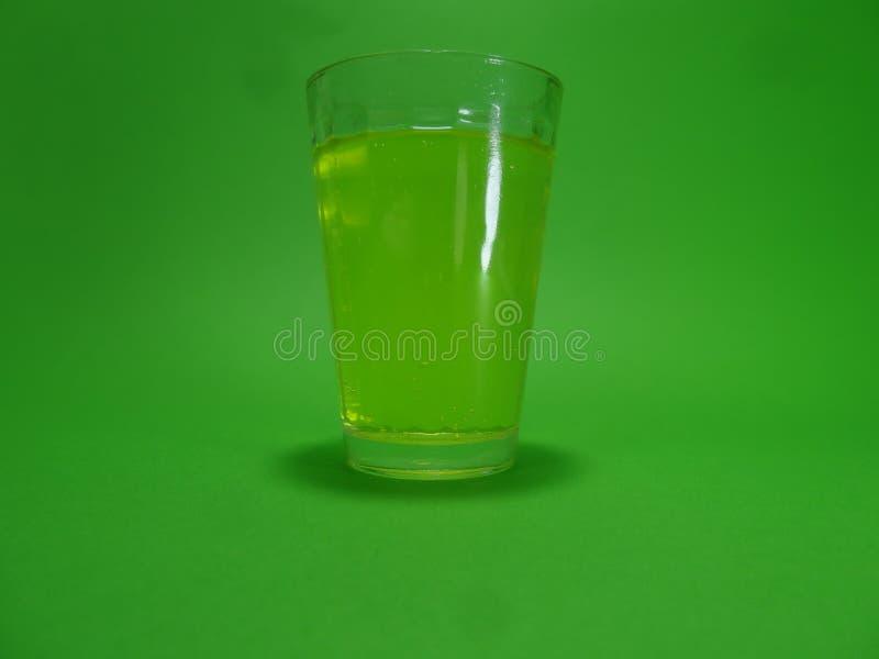 Absinthein a transparent glass on a green background. Liquour called absent on a transparent glass on a green background stock photo