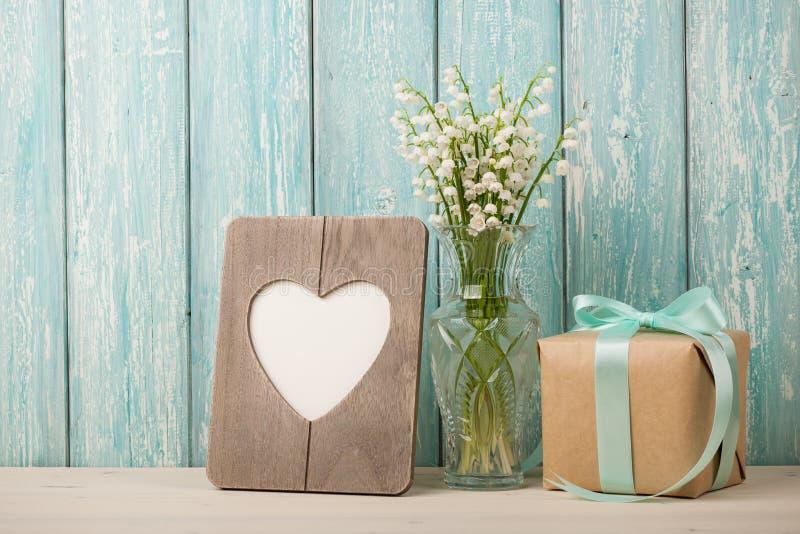 Lirios frescos del valle, del bastidor en forma de corazón y de la caja de regalo imagenes de archivo