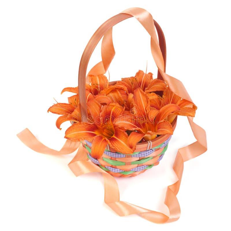 Lis oranges dans un panier en osier décoré du ruban photo stock
