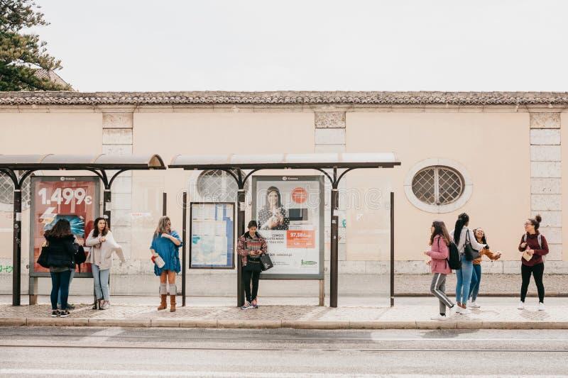Lisboa, el 18 de junio de 2018: Gente joven en el transporte que espera de la parada de autobús para Vida de ciudad ordinaria fotos de archivo