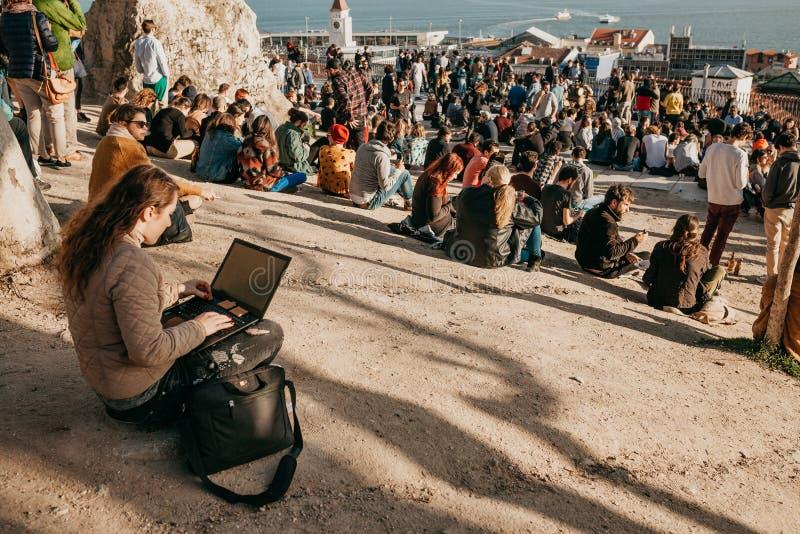 Lisboa, o 1º de maio de 2018: Um estudante da moça ou um blogger ou um freelancer trabalham no computador ou comunicam-se no Inte imagem de stock
