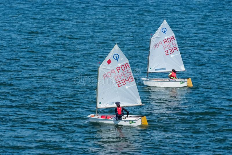 Lisboa, Portugal - 3 de abril de 2010: iate no mar azul Os atletas das crianças participam na raça no dia ensolarado Navigação do imagem de stock