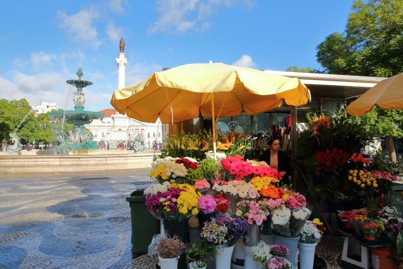 LISBOA, PORTUGAL - 4 DE NOVEMBRO DE 2017: Um florista no quadrado de Rossio com uma fonte e um monumento de Dom Pedro 4 no fundo fotografia de stock