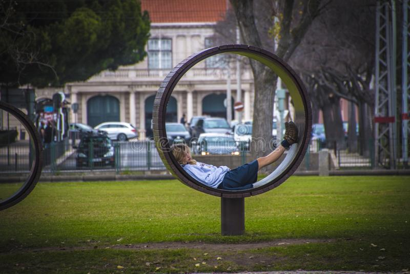 Lisboa, Portugal - em janeiro de 2018: Moça que descansa no parque em um banco incomum imagem de stock