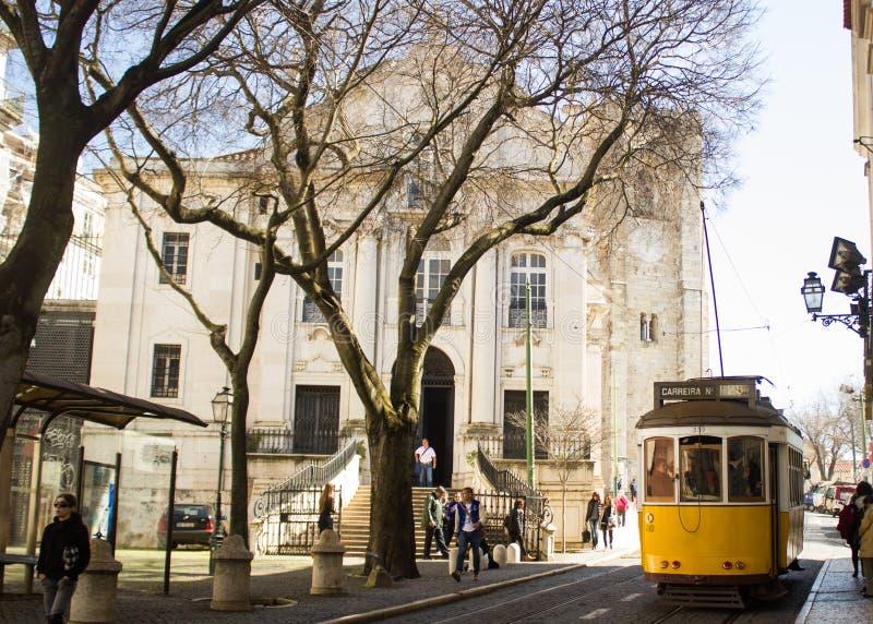 Lisboa, Portugal: fachada da igreja do NIO do ³ de Santo Antà e um bonde amarelo que passa perto foto de stock