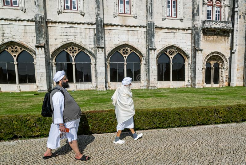 LISBOA, PORTUGAL. Indian tourists men in traditional clothes walking down the street against the walls of the castle royalty free stock photography