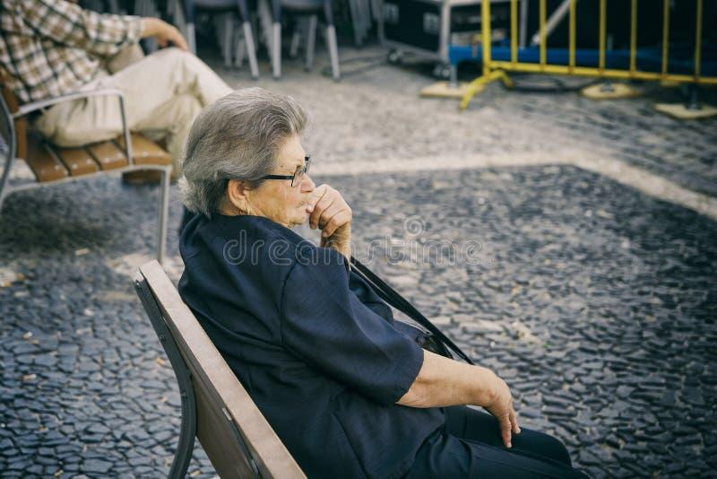 Lisboa, Portugal, o 23 de agosto de 2018: uma mulher triste idosa senta-se em um banco No fundo, dois homens estão sentando-se em imagem de stock royalty free