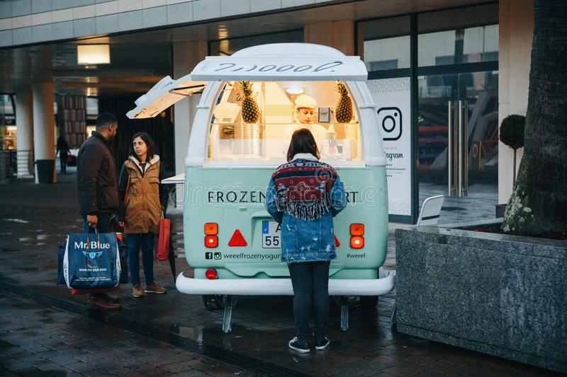 Lisbon, April 23, 2018: People buy frozen yogurt or ice cream from a street vendor next to fashion outlet called stock images