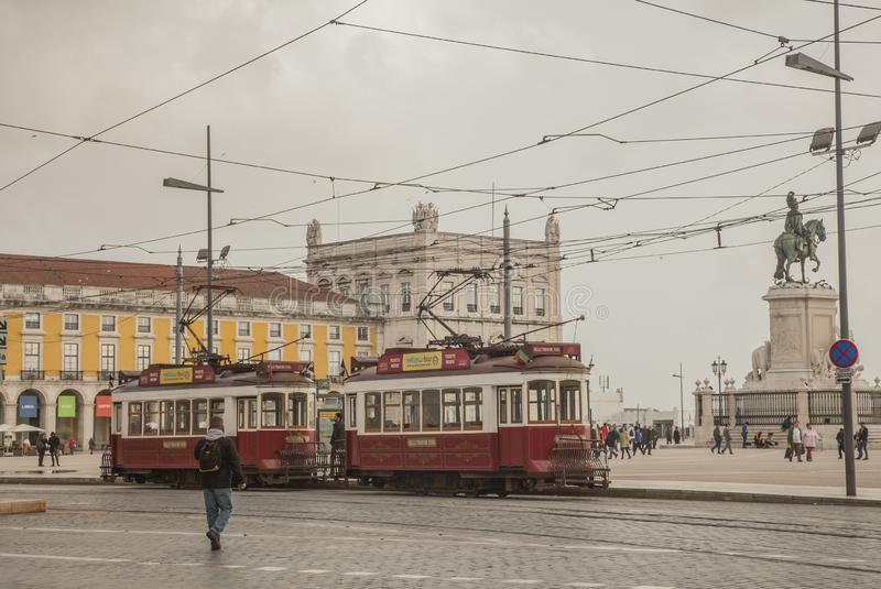 Lisbon - cloudy skies over the yellow square; trams. The Praça do Comércio is located in the city of Lisbon, Portugal. Situated near the Tagus river, the stock photography