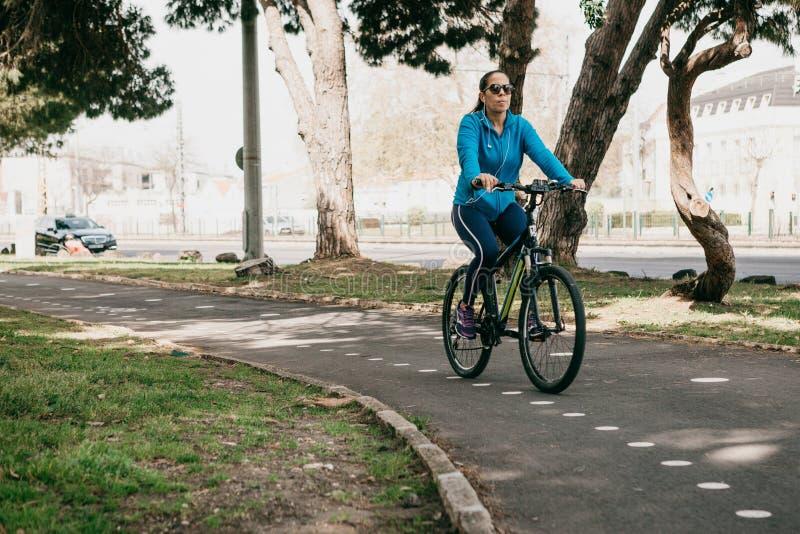 Lisbon, Czerwiec 18, 2018: Kobieta jedzie bicykl w miasto parku w Belem Codzienne sport aktywność miejscowy zdjęcia royalty free