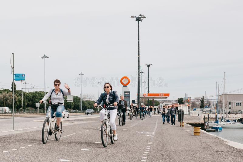 Lisbon, June 18, 2018: A group of positive people or tourists ride bicycles along a city street in the Belem area royalty free stock photo