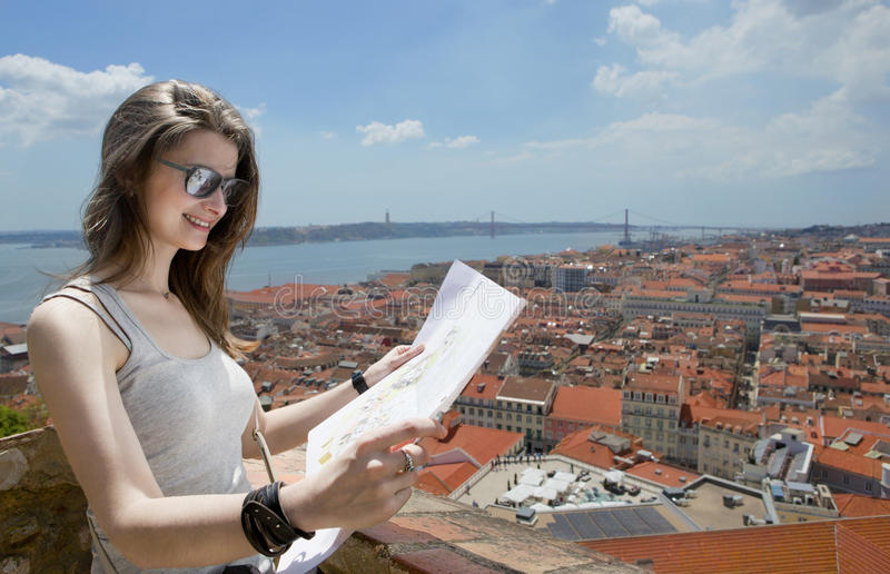 Lisbon. Lisboa. Portugal. Girl is standing near the Castelo de São Jorge and examines map of the city. Travel and Tourism royalty free stock photos