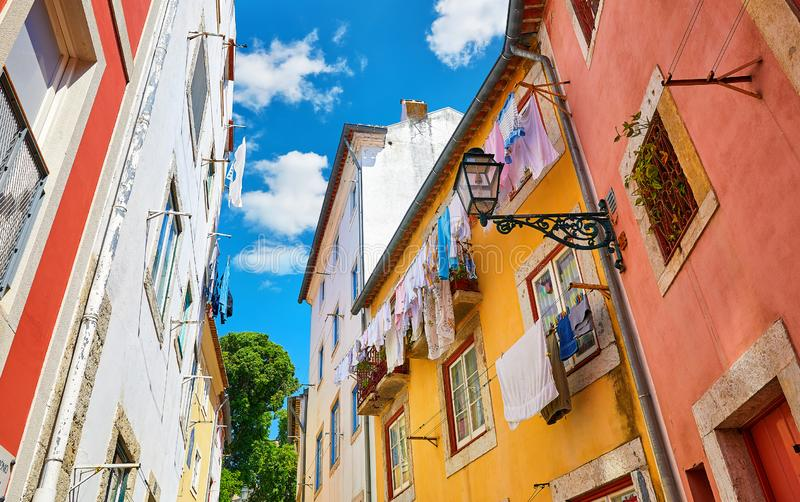 Lisbon, Portugal. Antique Alfama district with coloured. Houses on background of blue sky with clouds. Washed linen dry on ropes on streets between building stock photos