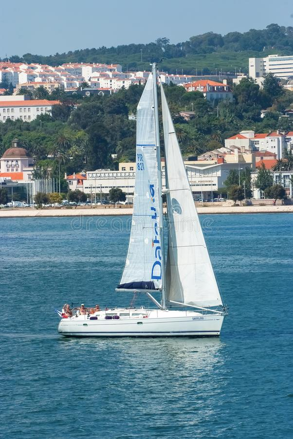 Lisbon, Portugal - April 03, 2010: sailing boat in sea on urban landscape. Sailboat with white sail sailing along sea royalty free stock photos