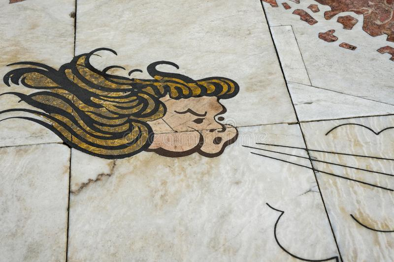 Lisbon, Portugal, August 22, 2018: Fragment of the mosaic of the wind rose. The marble tile shows the face of the wind God. Copy. Space royalty free stock image