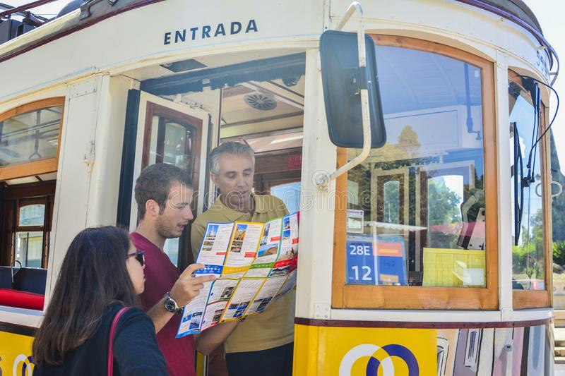 LISBON, PORTUGAL - AUGUST 07, 2017 :The tram driver shows the tourists the way on the map royalty free stock photography