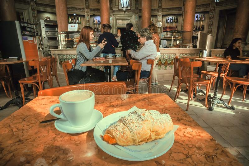 Breakfast with coffee and croissant in nice historical cafe with some customers of vintage place. LISBON, PORTUGAL: Breakfast with coffee and croissant in nice royalty free stock images