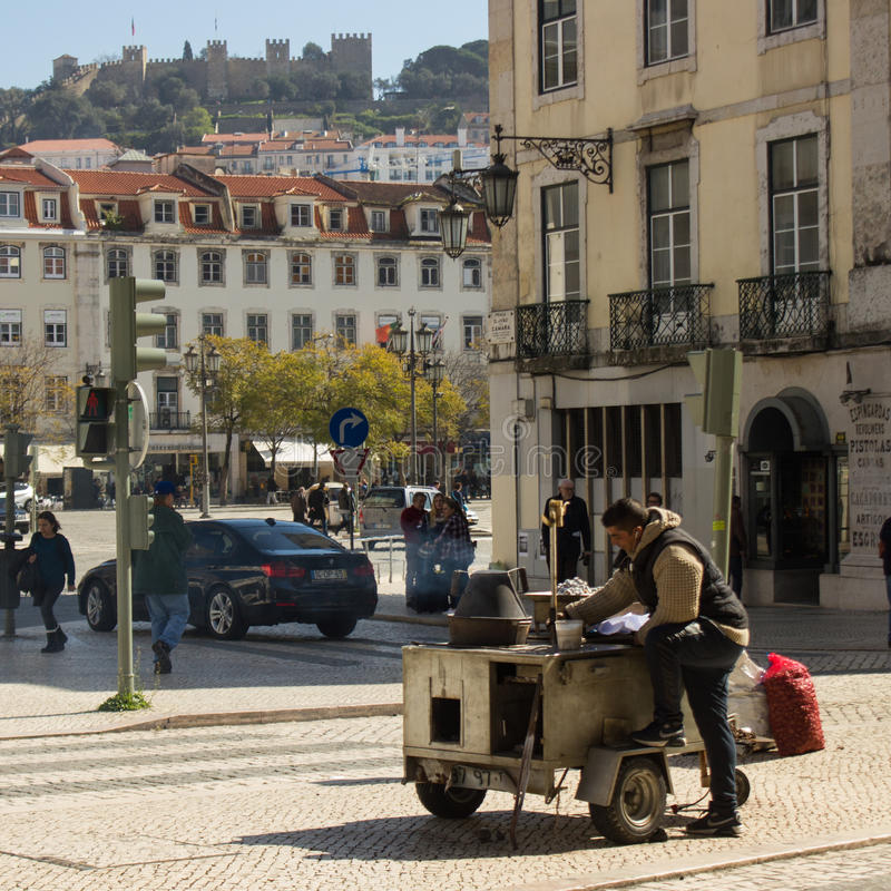 Lisbon, Portugal: hawker of roasted chestnuts. A young man selling roasted chestnuts in downtown Lisbon, Portugal, with a view to the St George Castle, where the royalty free stock photography