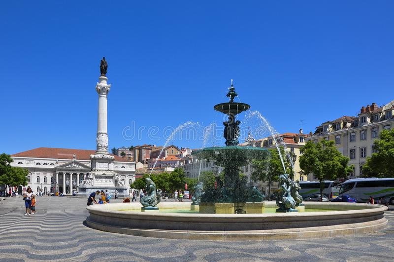 View of the Rossio Square with tourists walking by, in the pombaline downtown of the city of Lisbon, Portugal royalty free stock photo
