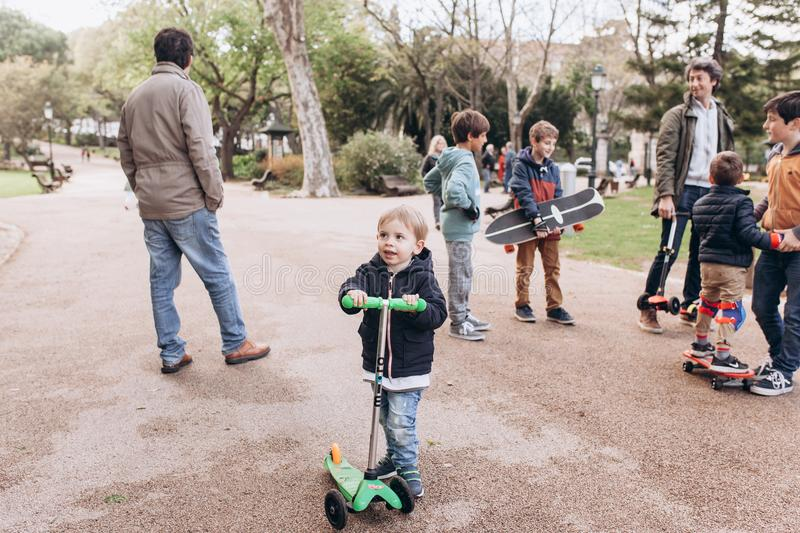 Lisbon, Portugal 01 may 2018: Caring fathers walk with their children and teach them to ride skateboards and scooters stock photos