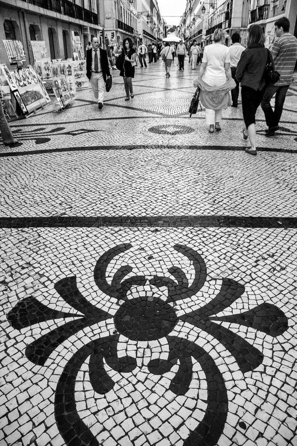 People walk on Rua Augusta street. LISBON, PORTUGAL - MAY 05, 2008: People walk on Rua Augusta street with traditional Portuguese pattern mosaic cobblestone stock photos