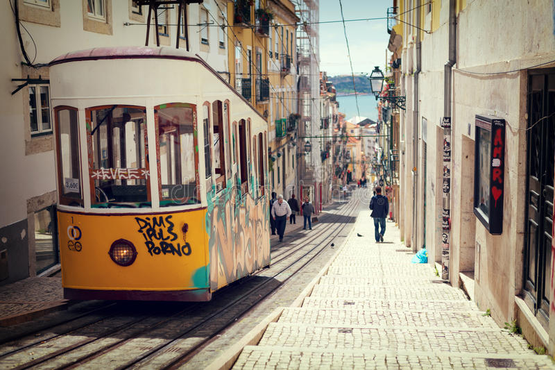 Lisbon, Portugal, 2015 04 17 - yellow tram - elevador da Bica st. Anding on top of the rails, vintage color style royalty free stock image