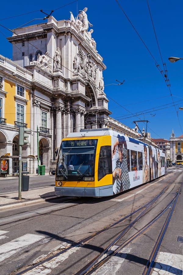 Lisbon, Portugalia: Carris nowożytny żółty tramwaj i Rua Augusta Uliczny Triumfalny łuk w Pracie robimy Comercio obraz royalty free