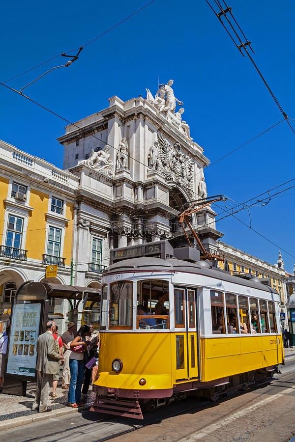 Lisbon, Portugalia: Carris rocznika żółty tramwaj i Rua Augusta Uliczny Triumfalny łuk w Pracie robimy Comercio aka Co fotografia stock