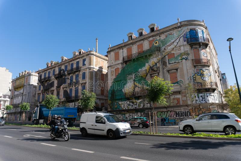 Lisbon Portugalia, Listopad, - 14,2017: Samochody jadą zaniechanym budynkiem z wielkim malowidłem ściennym w Lisbon, Portugalia zdjęcia stock