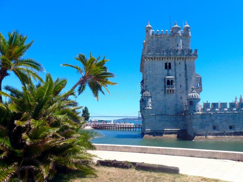 Lisbon Portugalia lub Torre de Belem z zielonymi drzewkami palmowymi, Belem wierza fotografia stock