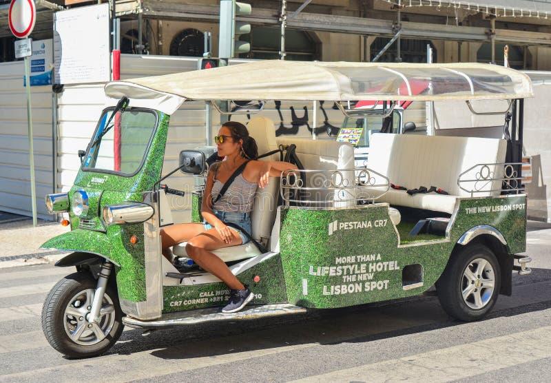 Lisbon Portugalia, Sierpień, - 05, 2017: Młoda dziewczyna kierowca taxi Tuk Tuk na drodze Lisbon Portugalia zdjęcie stock