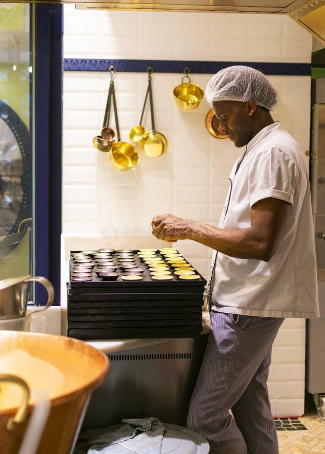 LISBONA, PORTOGALLO - 17 APRILE 2019: Il cuoco unico prepara le pasticcerie portoghesi tradizionali Pastel de Nata a Lisbona immagine stock libera da diritti