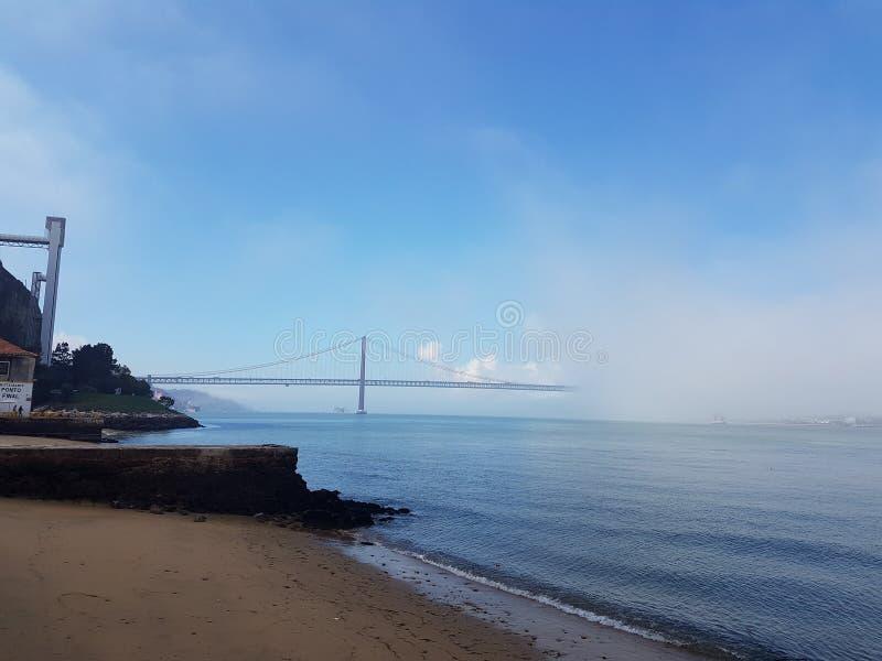 Lisbonne pont du 25 avril se dégageant après le matin brumeux photo libre de droits