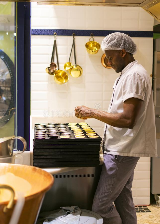 LISBONNE, PORTUGAL - 17 AVRIL 2019 : Le chef prépare les pâtisseries portugaises traditionnelles le Pastel de nata à Lisbonne image libre de droits