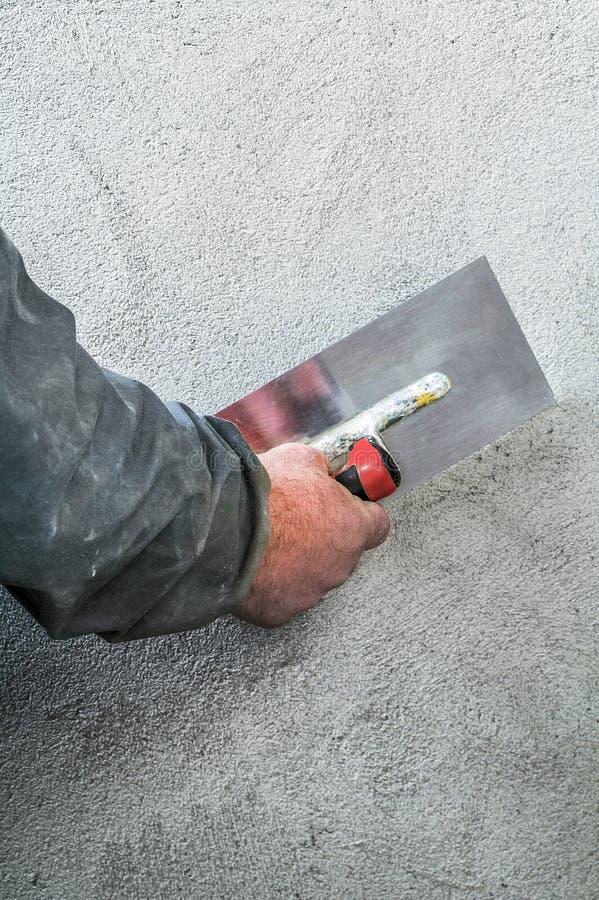 Lisciamento del muratore - intonacare muro di cemento da una st fotografia stock libera da diritti