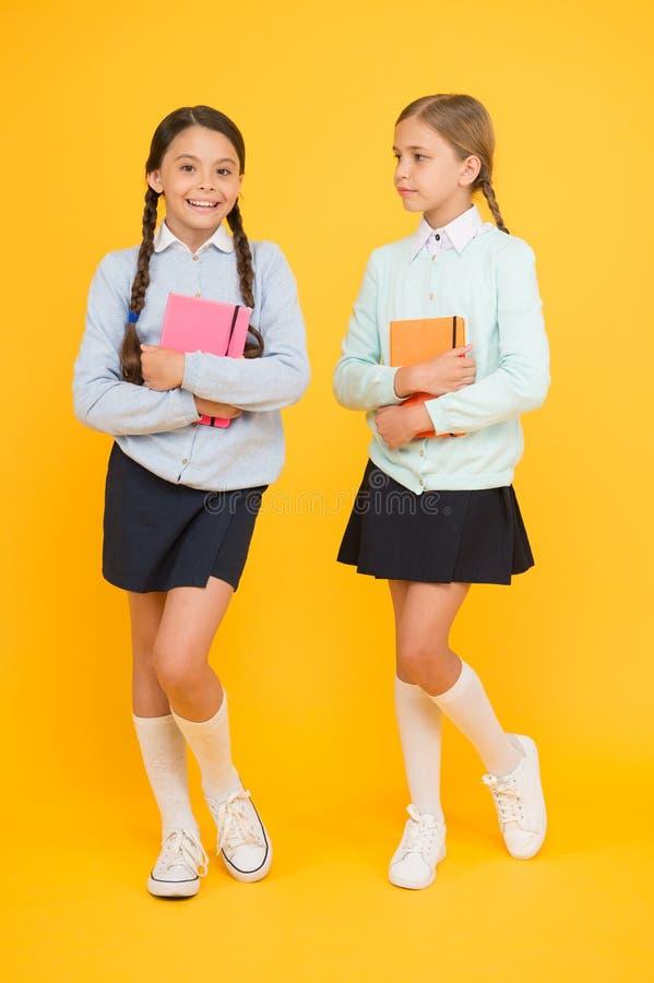Lisez l'avenir Petits enfants mignons pris des livres à lire de la bibliothèque sur le fond jaune Petites filles adorables photo libre de droits