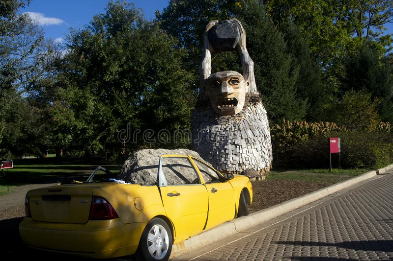 Troll throwing rocks. Lisle, Illinois, United States - October 23, 2018: Wooden figure of a troll throwing rocks at a car stock images