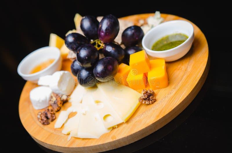 Liso-configuração da bandeja do queijo com variedade, figos, mel e porcas do queijo sobre o fundo concreto cinzento, vista superi imagem de stock royalty free