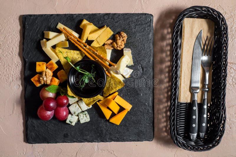 Liso-configura??o da bandeja do queijo com variedade, figos, mel e porcas do queijo sobre o fundo concreto cinzento, vista superi foto de stock