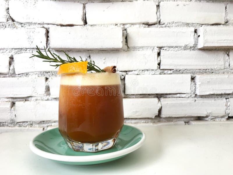 Liso negro, zumo de naranja de la mezcla del café de hielo en vidrio en el verde foto de archivo libre de regalías