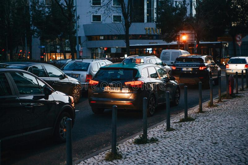 Lissabon April 25, 2018: Många bilar på tvärgatorna i aftonen Trafik i staden royaltyfria foton