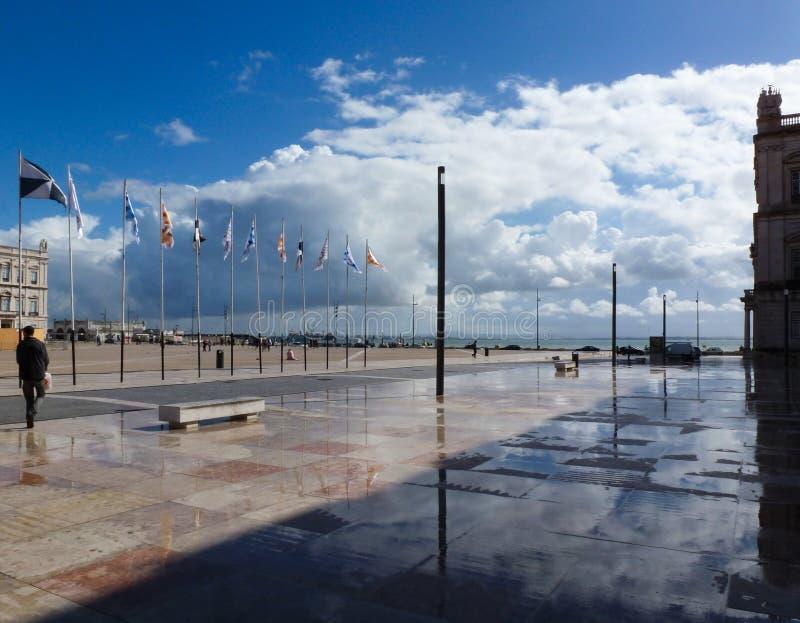 Lissabon kommersfyrkant med blå himmel, vita moln och reflexioner arkivfoto