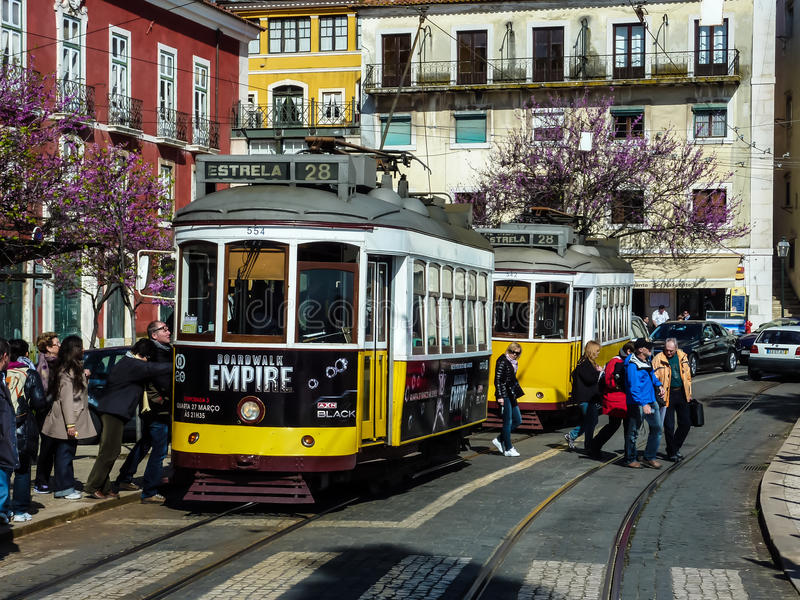 LISSABON PORTUGAL - APRIL 7, 2013: Turister som skriver in den gula spårvagnen, Lissabon, Portugal arkivfoton