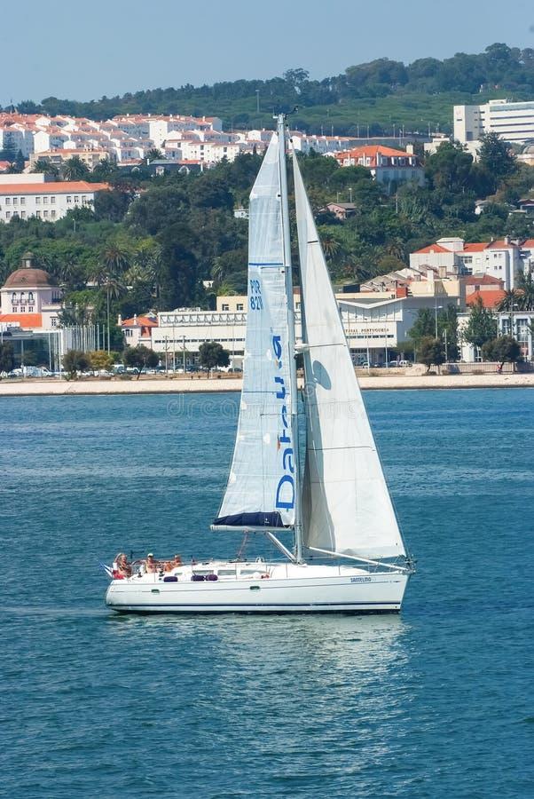 Lissabon, Portugal - April 03, 2010: varende boot in overzees op stedelijk landschap Zeilboot met wit zeil die langs overzees var royalty-vrije stock foto's