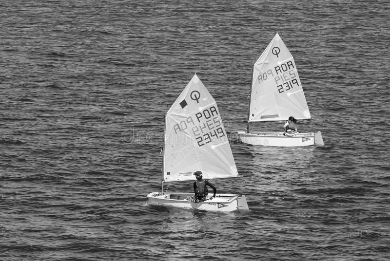 Lissabon Portugal - April 03, 2010: yachter i det blåa havet Barnidrottsman nen deltar i lopp på solig dag Havssegling arkivbild